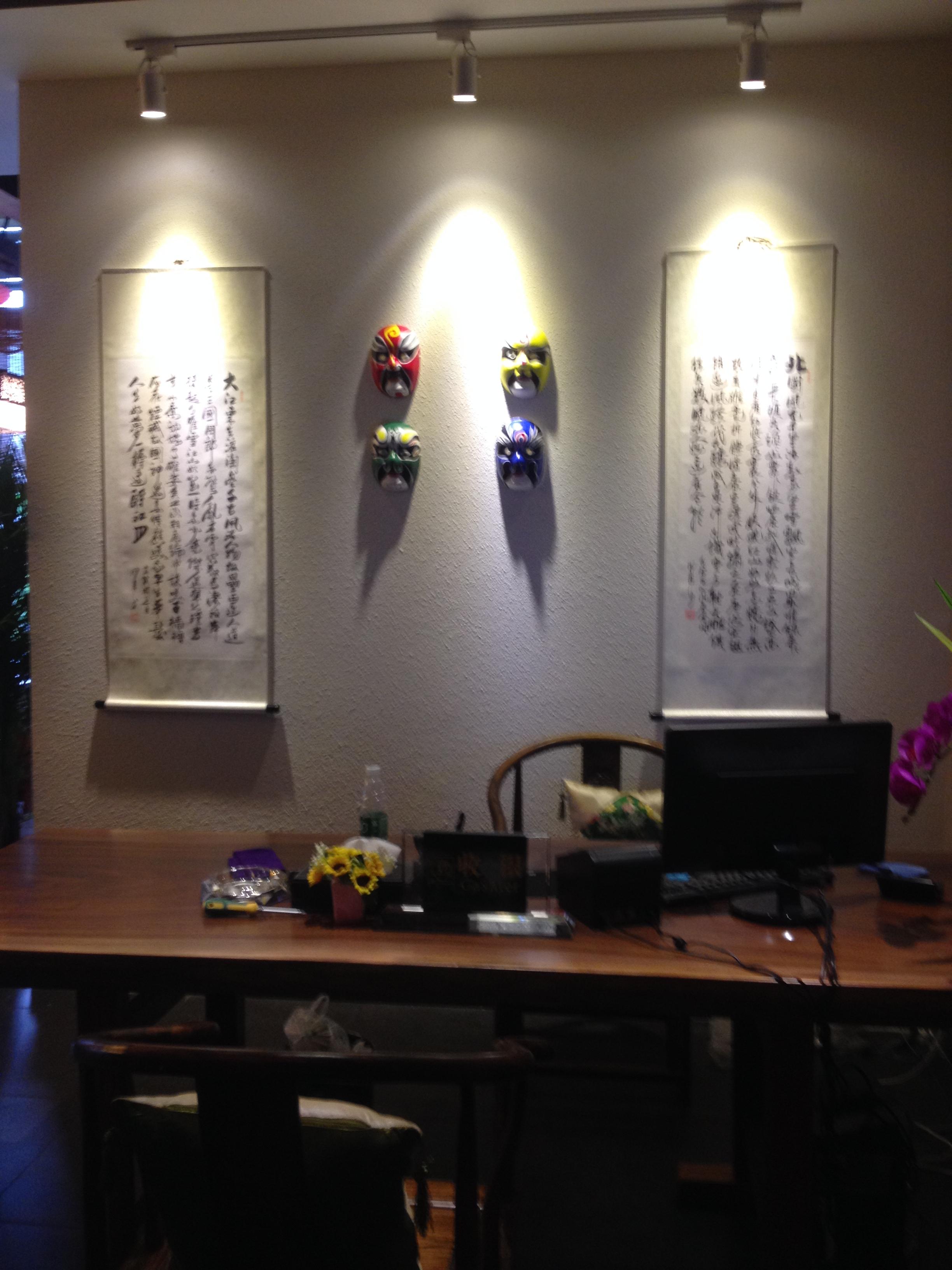 青砖的墙面,木质柜体,定制的家具和随意摆放的植物,都诠释了一种优雅宁静, 古朴的情怀,贴合茶文化糅合了中国儒、道、佛诸派思想,独成一体,芬芳而甘醇。  办公空间除了用字画呼应古朴的风格,另外点缀的戏曲脸谱,鲜明的色彩,使得整个氛围多了一抹趣味。  门采用了玻璃这种现代元素,结合门把手上的祥云,将现代和古代做了一个完美衔接,青砖背景墙上面浅浅的小青苔,滴答滴答的水滴落入石槽里,让人不禁想起江南的烟雨,顶上的红色油纸伞是细雨中的一抹妖娆,在袅袅的茶香中,变得幽怨又迷蒙。 也许这就是茶吧,淡淡中悠远的让人猜不
